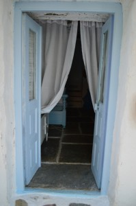 The stone door outlined with the light blue wooden frame typical of Cycladic houses