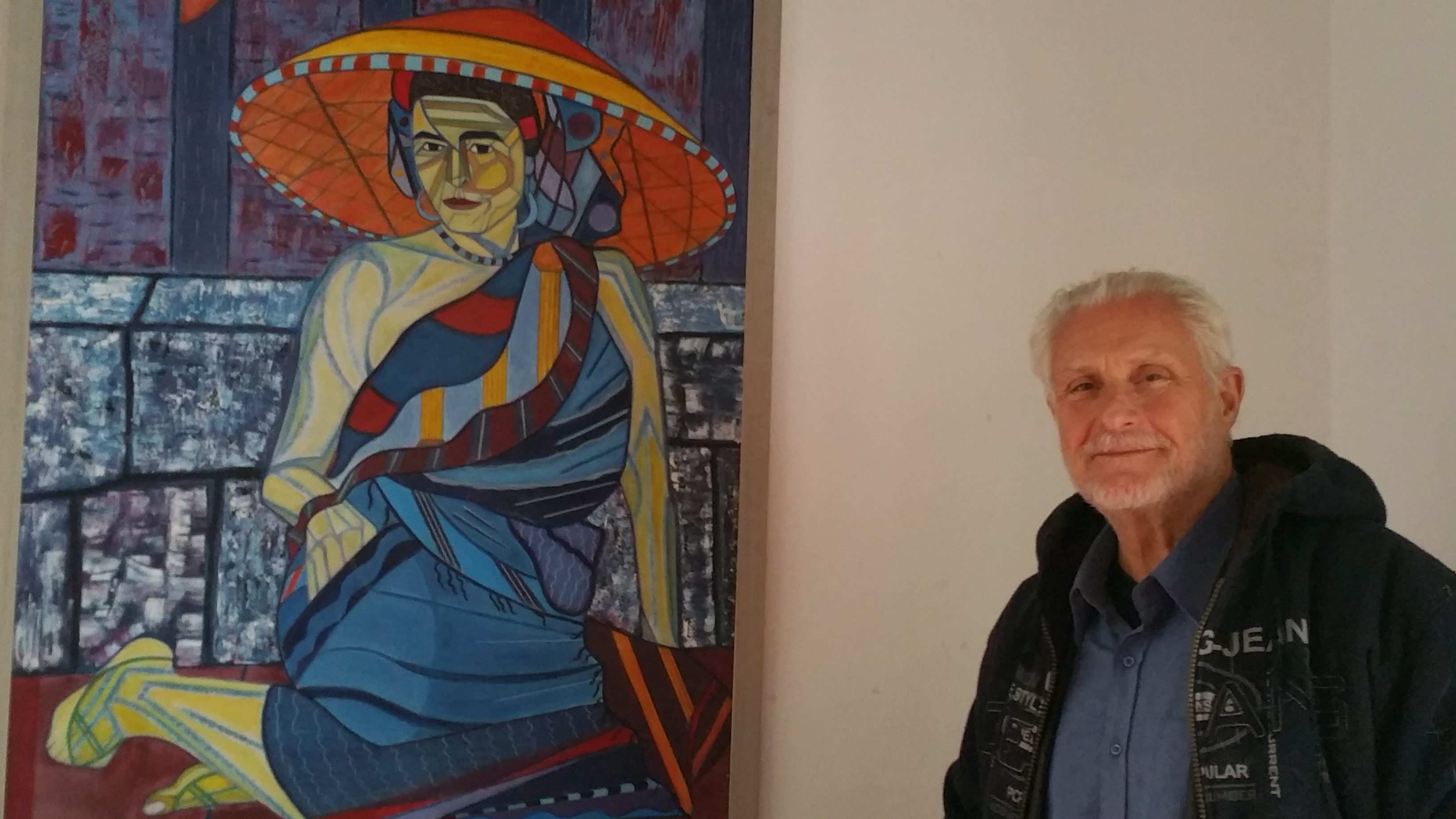 Barry Tagrin besides his portraits within the exhibit space of the Hellenic International Studies of the Arts.
