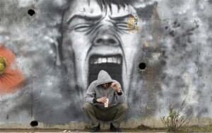 A man drinks coffee in front of a mural near the coastal town of Kalamatta in the Messinia area of Greece